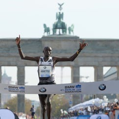 Kenya's Dennis Kimetto crosses the finish line to win the Berlin marathon in a world record time in Berlin, Germany, on Sunday, (Kimetto set a world record of 2h, 2min and 57 seconds.)