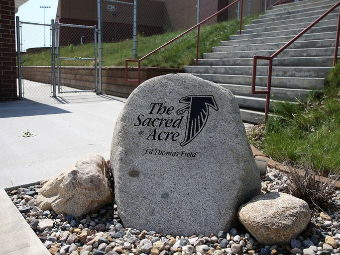 A stone serves as a tribute to Ed Thomas near the entrance to the Aplington-Parkersburg football field in Parkersburg, Iowa. Thomas was killed by a former player of his, Mark Becker, who was struggling with delusions at the time he shot Thomas in a makeshift weight room outside of the school in 2009.
