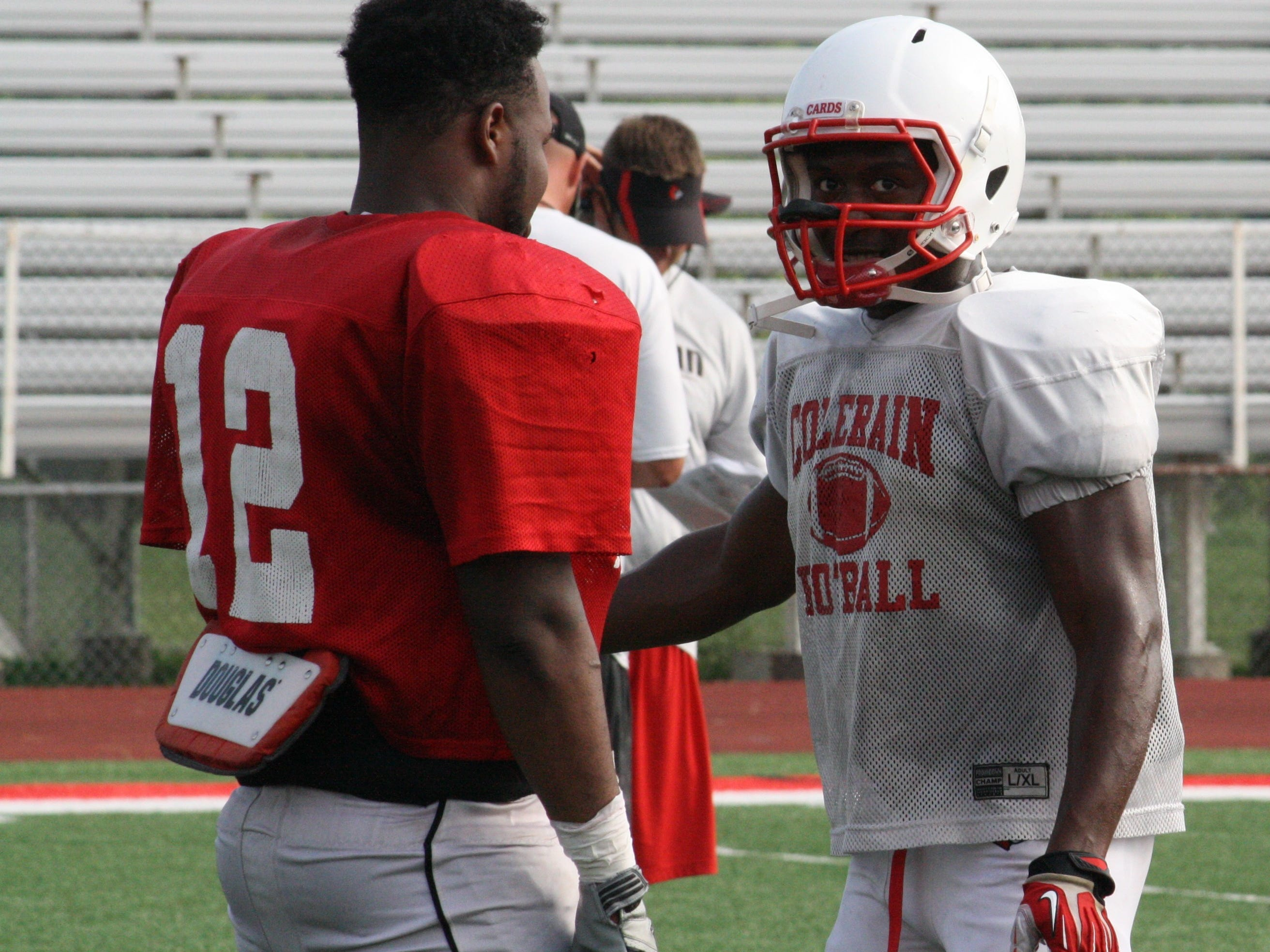 Two of Colerain High School's senior football captains, Demetrius Colbert, left, and Jordan Asberry chat during a water break at preseason practice Aug. 19. Colbert, a linebacker, was named first-team All-GMC in 2013, while Asberry rushed for 480 and caught six balls for 123 yards last season.