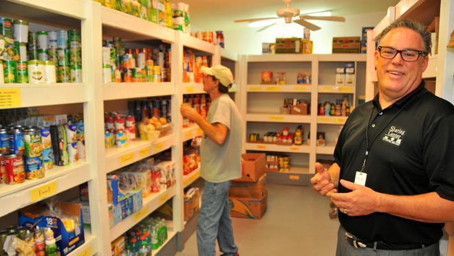 David Brubaker, president and chief executive officer of the Central Brevard Sharing Center, said the $32,000 that Brevard County allocated to the center for its emergency food program is important to supplement food donations the center receives. Behind him, Tom Gibbs unpacks food in center's pantry in Cocoa.