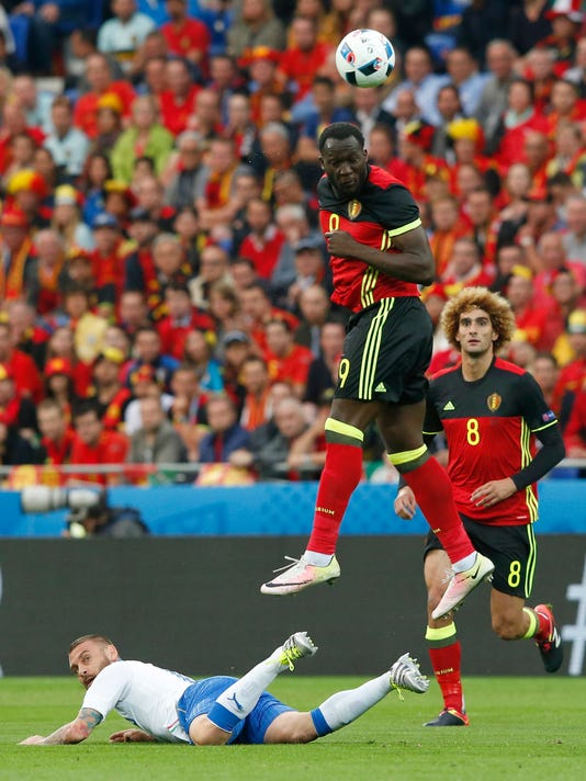 Belgium's Romelu Lukaku jumps for an header as Italy's Daniele De Rossi lies on the pitch during the Euro 2016 Group E soccer match between Belgium and Italy at the Grand Stade in Decines-Charpieu, near Lyon, France, Monday, June 13, 2016. (AP Photo/Antonio Calanni)