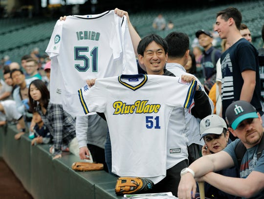 Fans hold Ichiro Suzuki jerseys from the Seattle Mariners