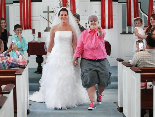 Mysti Brooks, right, shows off her ring while walking back up the aisle with her wife Jennifer Snider after sealing their blessing ceremony at the First Congregational United Church of Christ on Saturday, June 28, 2014. The couple jumped on the opportunity to exchange vows on Thursday at the City County Building in downtown after picking up their marriage license the day before the stay banning same sex marriage took effect Friday evening. The ceremony was scheduled for Saturday with no one knowing the couple actually got married.