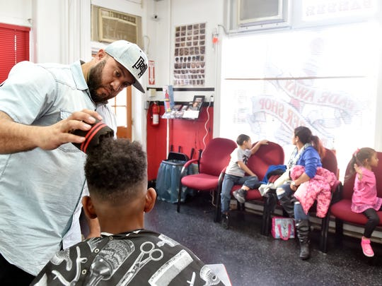 Isaac Mantilla gives Northeastern Middle School ninth-grade student Eric Davenport, 14, a free haircut at Fade Away Barber Shop in York. For three years, shop owner Isaac Mantilla has been rewarding students who get As and Bs on their report cards by giving away free haircuts.