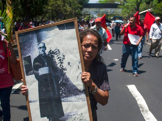 In this March, 24, 2015 file photo, Maria del Pilar Perdomo, 58, holds up a framed portrait of slain Archbishop of San Salvador, Oscar Arnulfo Romero, during a procession to mark the 35th anniversary of his assassination in San Salvador, El Salvador. Pope Francis has cleared the way for slain Salvadoran Archbishop Oscar Romero to be made a saint, declaring that a churchman who stood up for the poorest of the poor in the face of right-wing oppression should be a model for Catholics today.