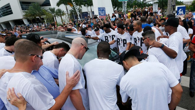 Miami Marlins players and staff surround a hearse carrying the body of pitcher Jose Fernandez as it leaves Marlins Park on Wednesday.