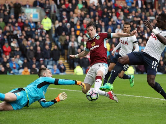 Tottenham Hotspur's Moussa Sissoko, right, battles for the ball with Burnley goalkeeper Tom Heaton and Stephen Ward, during the English Premier League soccer match between Burnley and Tottenham Hotspur, at Turf Moor, in Burnley, England,  Saturday April 1, 2017. (Nick Potts/PA via AP)
