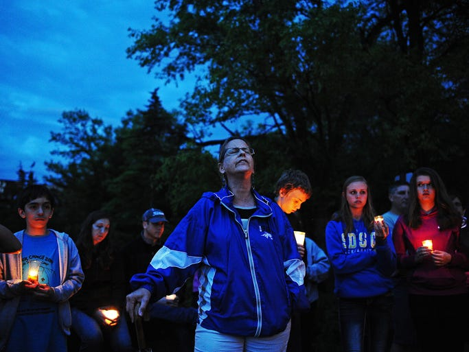 Tammy Smith, a neighbor of 9-year-old Joey Cavallaro, whose body was found in Split Rock Creek on Saturday morning after he went missing on Friday, sings during a candlelight vigil Saturday, May 31, 2014, in memory of Cavallaro at Split Rock Park in Garretson, S.D. More than a hundred family members and friends showed their support with candles and songs on Saturday night during the vigil.