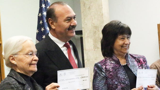 Marcos Bucio, center, consul general of Mexico in El Paso, presents scholarship checks to University of Texas at El Paso President Diana Natalicio, left, and Jenny Giron, vice president for information technology and chief information officer for El Paso Community College during a ceremony Tuesday at the Mexican Consulate in Downtown El Paso.