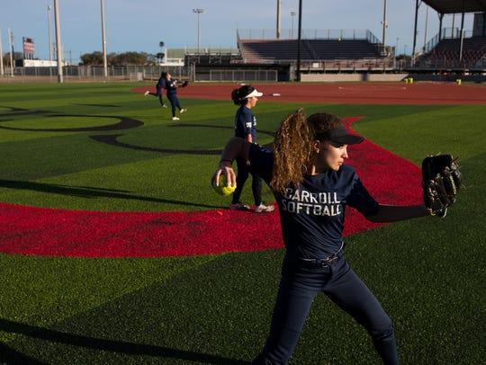 Carroll softball players throw balls as they warm up