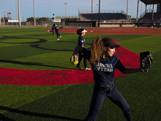 Carroll softball players throw balls as they warm up during practice at Cabaniss Softball Field on Wednesday, Jan. 24, 2018.
