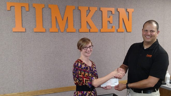 Kylie Herbert of Habitat for Humanity of Anderson County receives a check for $75,000 from Randy Dunn of Timken on behalf of the Timken Foundation.