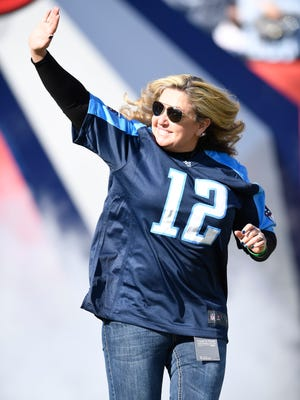 Heather Melton, who's husband was killed at the Vegas shooting, waves as she enters the field at Nissan Stadium Sunday, Dec. 3, 2017 in Nashville, Tenn.