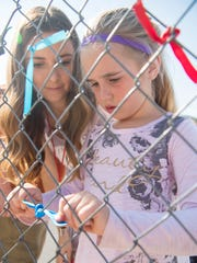 A student gets help tying a ribbon on the schoolyard fence in honor of Merilee Jones.