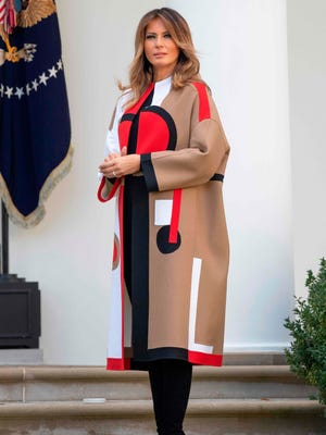 First lady Melania Trump pulled another striking coat out of her closet for the turkey pardoning ceremony on Nov. 20, 2018 in the Rose Garden. Her coat featured tan, black, white and red colors in a pattern similar to a modern-art painting. Underneath she wore black top, leggings and high-heeled suede boots.