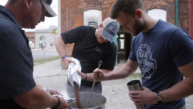Instructor Ari Levinsohn, left, and Craig Collier, center, add malt extract to a vat of brewing beer as Colin Reardon, right, stirs, Saturday, July 16, 2016, at the REO Brew School in Lansing's REO Town.