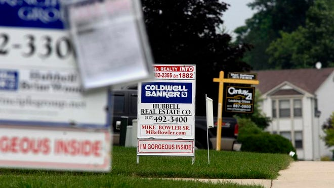 Three for sale signs on homes on Moorwood in Holt. (photo by Rod Sanford)  For story on foreclosures.