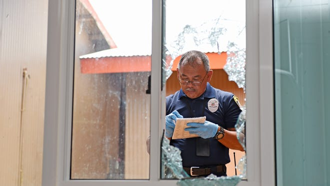 In this file photo, a police officer takes notes at L.P. Untalan Middle School after it was broken into and vandalized.