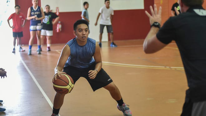 A student learns to maintain court awareness by counting his coach's fingers while dribbling at the Guam Hoops Academy opening day at the Phoenix Center in Mangilao on June 3.