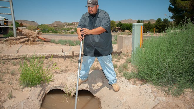 EBID 'ditch rider' Joseph Karpac uses a flow probe to monitor the speed of water coming out of the Picacho Main Canal in June 2015.