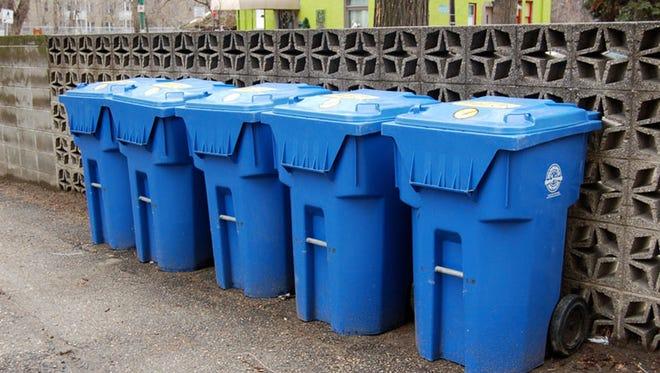 Recycling bins line an alleyway.