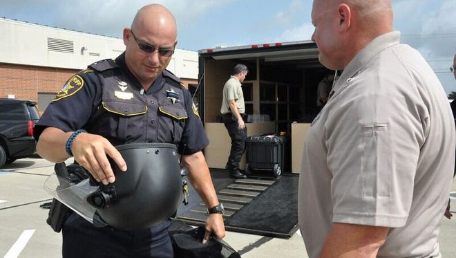 Bossier Parish Deputy Jessie Bearden and Sgt. Clint Robins, members of the newly formed riot control unit, gather civil unrest gear Monday in preparation for deployment to Baton Rouge.