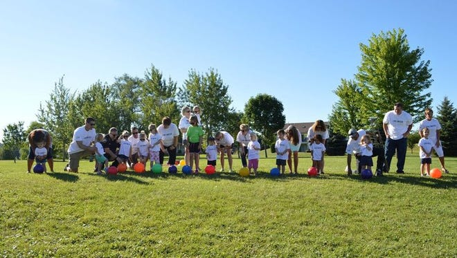 The Board of Directors for the United Way Manitowoc County line up with children to kick off the annual campaign with brightly colored balls during the Day of Action Saturday at Washington Park in Two Rivers.