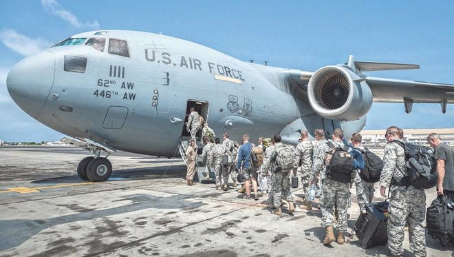 A group of 30 U.S. military personnel, including Marines, airmen and soldiers from the 101st Airborne Division, board a U.S. Air Force C-17 Globemaster III at Léopold Sédar Senghor International Airport in Dakar, Senegal, on Oct. 19. The service members were bound for Monrovia, Liberia, where U.S. troops are helping to provide the U.S. response to the Ebola outbreak in West Africa.