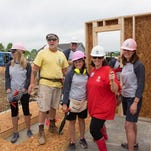 GNAR director Julie Casassa, left center, and GNAR president Denise Creswell, right, join future homeowner Cindy Bryant, center, on the first day of building her new home.