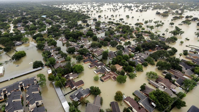 In this Aug. 29, 2017, file photo, water from Addicks Reservoir flows into neighborhoods as floodwaters from Tropical Storm Harvey rise in Houston.