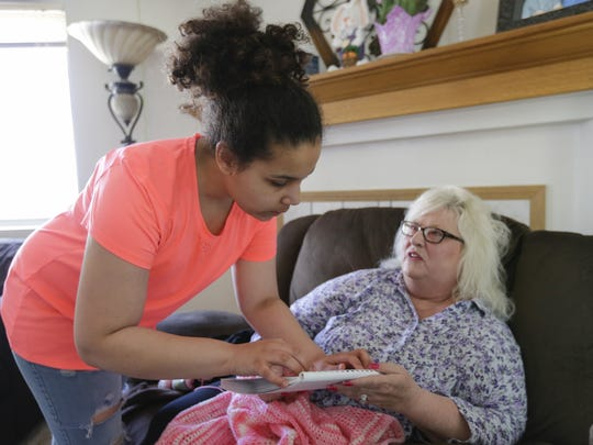FILE - Isabella, then 16, shows her mom Becky how her braille reading is coming along on her new braille book in the Brooks' living room on March 28, 2018, in Manitowoc. The brain tumors Isabella struggles with cause vision problems, making it hard for her to read.