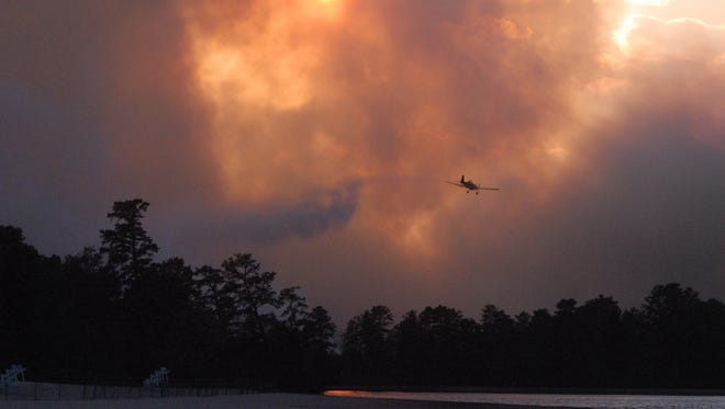 File photo: An airplane drops water on a forest fire at Atsion Lake in Shamong Twp., N.J. on Tuesday, Oct. 21, 2008.