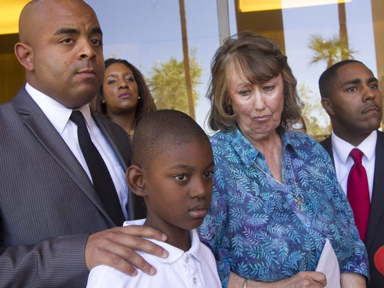 Malacai Washington, 9, speaks alongside (from left) civil rights leader Rev. Jarrett Maupin, his teacher Pam Aister, and attorney, Benjamin Taylor, at the Arizona State Capitol in Phoenix on Tuesday, October 14, 2014. Aister alleges she was fired after defending Malacai who was being bullied and singled-out racially by his classmates. She says she may sue the school district.
