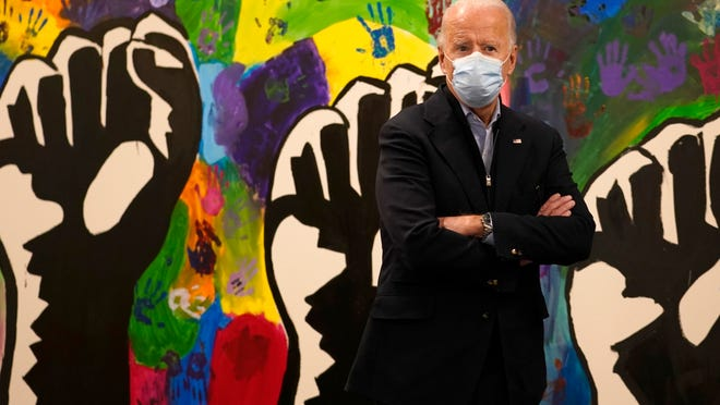 Democratic presidential candidate former Vice President Joe Biden pauses in front of a mural during visit to The Warehouse teen center in Wilmington, Del., Tuesday, Nov. 3, 2020.
