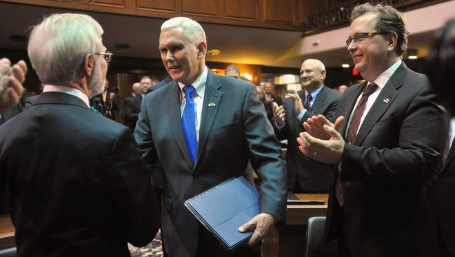 Indiana Gov. Mike Pence shales hands on both sides of the aisle as he walks in to deliver the 2014 State of the State Address in the House Chamber at the Indiana Statehouse Tuesday, Jan. 14, 2014.