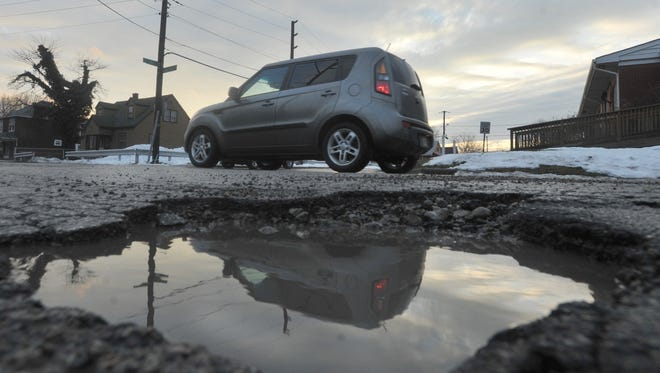 A pothole on the side of the road looks big enough to swallow small vehicles on Belmont Ave. at Ray Street, Monday January 13, 2014.