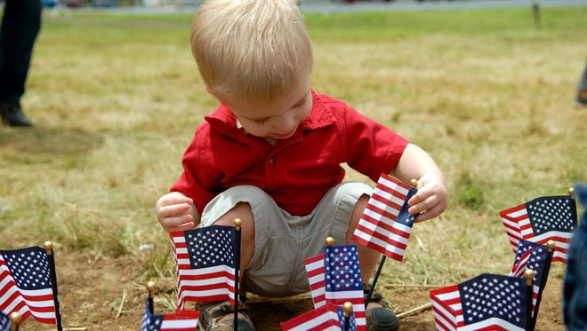 Jordan Keller, 20 mo., selects a flag during the dedication of Prosperity Park at America Place's second annual Independence Day celebration and cookout in the new park in Jeffersonville, Ind.  July 03, 2014