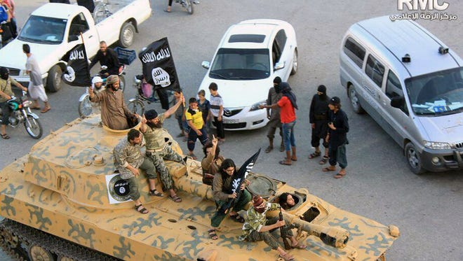 Fighters from Islamic State group sit on their tank during a parade in Raqqa, Syria.