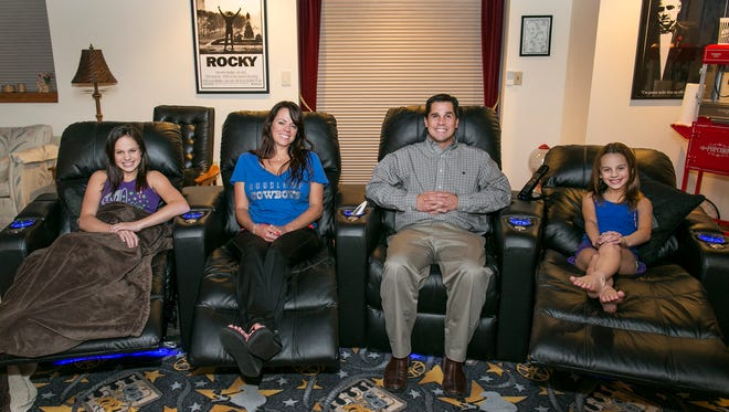 The Perrone family — from left, Meghan, Gretchen, Tom and Sara — in the theater room of their Victor home.