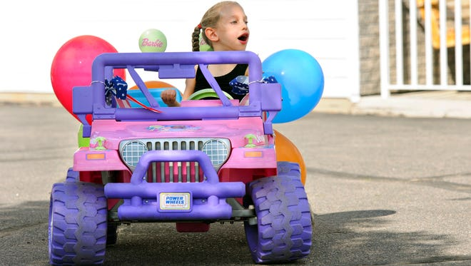 Isabel Salzbrun, 6, rides in her new remote-controlled car driven by her father, Jeremy, on Tuesday at her day care in St. Augusta.
