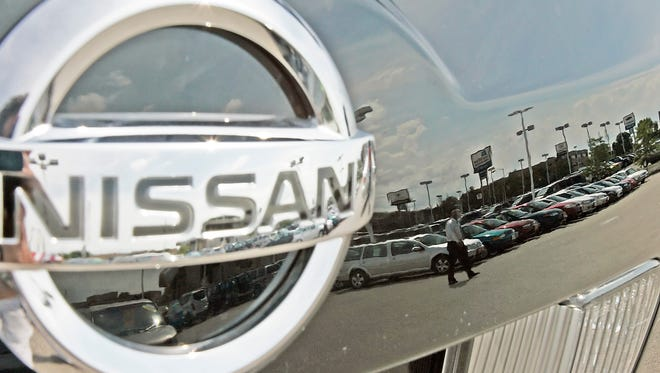ORG XMIT: NY108 FILE - A Nissan dealership is reflected in the hood of a car in this July 25, 2005 file photo taken in West Allis, Wis. Nissan is recalling 2.14 million vehicles in the U.S., Japan, Europe and Asia, including the popular March and Mycra subcompacts, for an ignition problem that may stall the engine _ its third-largest recall ever. (AP Photo/Morry Gash, File)