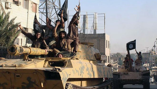 Fighters from the Islamic State militant group parade in Raqqa, Syria.