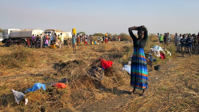 A displaced woman stands by her washing at the U.N. compound where she has sought shelter in Bentiu, in oil-rich Unity state, in South Sudan on Dec. 24, 2013.