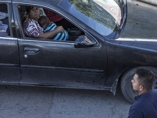 A mother holds a child in her arms in Nogales, Mexico,