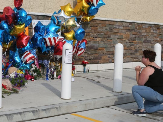 Emily Hill of Maryland pauses in front of a growing memorial to Cpl. Stephen Ballard as business returns to the Bear Wawa Saturday morning nearly 3 full days after the Delaware State Police trooper was shot and killed in the parking lot.