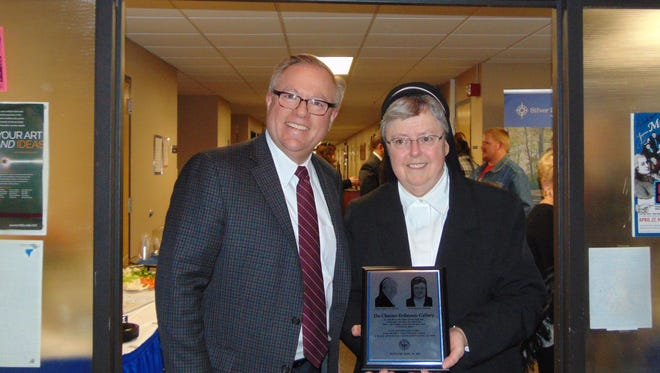 Dr. Chris Domes, president of Silver Lake College, presents long-time art professor Sister Mariella Erdmann with a plaque during the dedication of the college's art hall gallery on Thursday. The gallery honors Sister Mariella and Sister Andrée Du Charme, also a long-time art professor. Both are retired from Silver Lake College. The hall will be called the Du Charme Erdmann Gallery. Sister Andrée was unable to attend.
