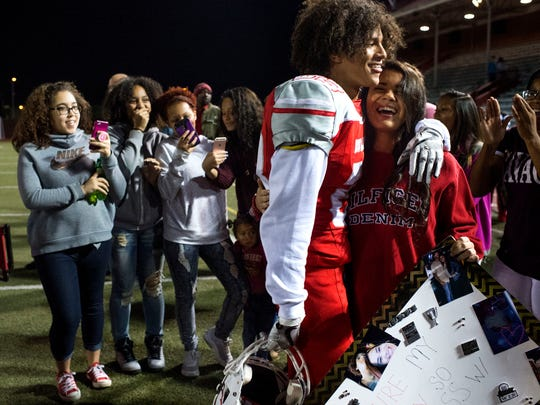 Ayah Almoudai and her boyfriend Christian Bell (23) embrace after she surprised him after the game with a sign inviting him to Santa Switch, a school dance. Bosse High School defeated Boonville High School, 20-14, in their first sectionals game at Enlow Field in Evansville, Ind., on Friday, Oct. 20, 2017.