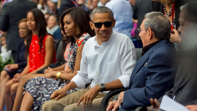 President Barack Obama, with members of the first family, talks with Cuban President Raul Castro before Tuesday's exhibition in Havana.