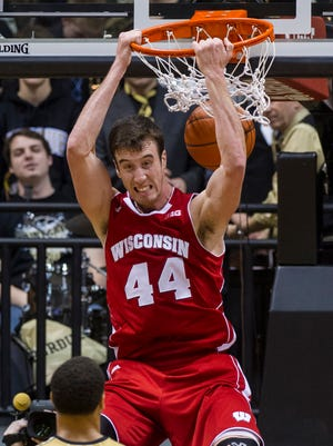 In this Jan. 25, 2014, file photo, Wisconsin's Frank Kaminsky slam dunks the ball late in the second half of a game against Purdue in West Lafayette, Ind.  The 2013-14 season was known as the year of the freshmen and for good reason. This season, there are fewer star players, putting the focus on the team instead of individual players.