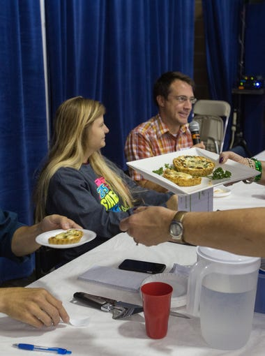 Columnist Kyle Munson is served by Rose Houston of West Des Moines in the Des Moines Register Hog (and Corn) Heaven food contest at the Iowa State Fair in Des Moines, Iowa, Wednesday, Aug. 19, 2015.